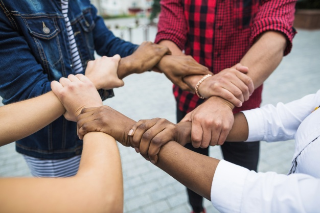 anonymous-multiracial-people-stacking-hands_23-2147664377